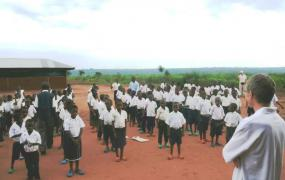 Kids singing in front of school buildings.