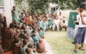 Pygmäenkinder in einer Schule: Lenka und Johnny mit Übersetzerin zeigen Bibelgeschichten.