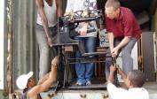 Wolfgang, Mathew & helpers unload a shoemaker machine.