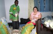 Theophile & Madlen prepare food-bags for the orphan children in Kikimi.