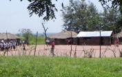School of Kakondo (neighboring village of Mushapo): View on the schoolyard with the school buildings in the background. In the area, the buildings are built with wooden sticks, mud and thatched roofs.