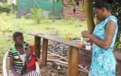 Blandine gives free medicine to sick village child.