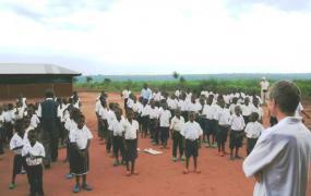Kids singing in front of school buildings.